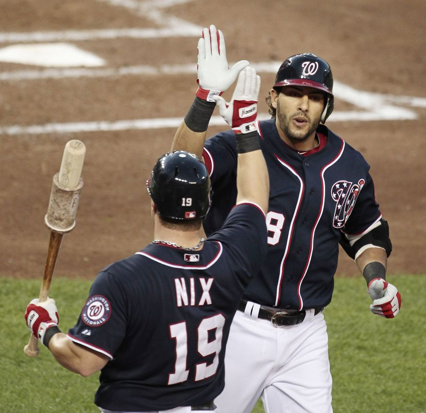Washington Nationals Michael Morse is greeted at home by teammate Laynce Nix after hitting a home run against Cincinnati Reds starting pitcher Mike Leake during the third inning Tuesday, Aug., 16, 2011 in Washington. (AP Photo/Pablo Martinez Monsivais)
