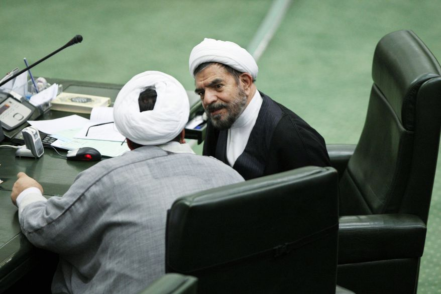 ASSOCIATED PRESS Iranian cleric lawmaker Hossein Hashemian (right) talks with a colleague in parliament in Tehran on Wednesday. Iran's internal power struggles are shifting into election mode with hard-line political forces banding together to groom candidates for next year's parliamentary elections and punish allies of President Mahmoud Ahmadinejad.