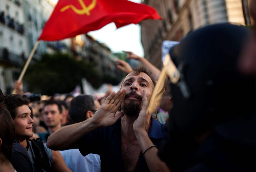 ASSOCIATED PRESS A demonstrator shouts slogans against the visit of Pope Benedict XVI in Madrid on Wednesday. The pope is due to arrive Thursday to celebrate World Youth Day, and thousands of protesters railing against his visit marched through central Madrid.