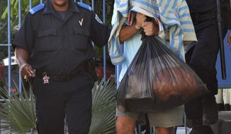 Gary V. Giordano, the U.S. citizen being held in Aruba in the disappearance of Robyn Gardner, 35, covers his head while being led to jail from a police station in San Nicolas, Aruba, on Aug. 15, 2011. (AP Photo)