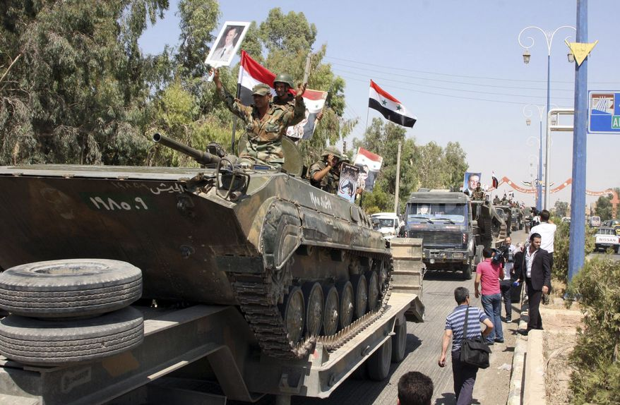 In this photo taken on a government-organized tour, Syrian soldiers atop armored personnel carrier cheer on their way out of the eastern city of Deir el-Zour, Syria, on Aug. 16, 2011. (Associated Press)