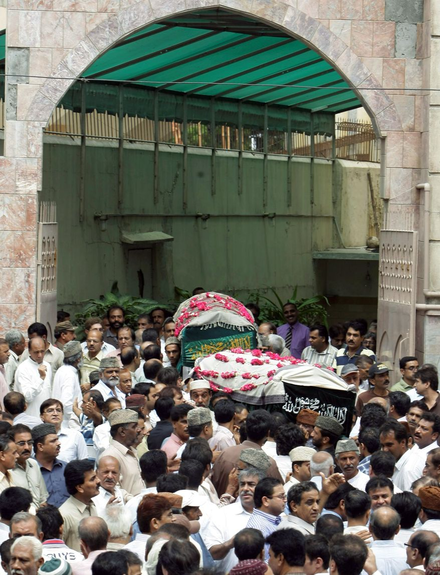 Mourners carry the bodies of a former lawmaker of the ruling Waja Karim Dad party and his friend at their funeral in Karachi on Thursday. They were fatally shot in violence carried out by gang members. (Associated Press)