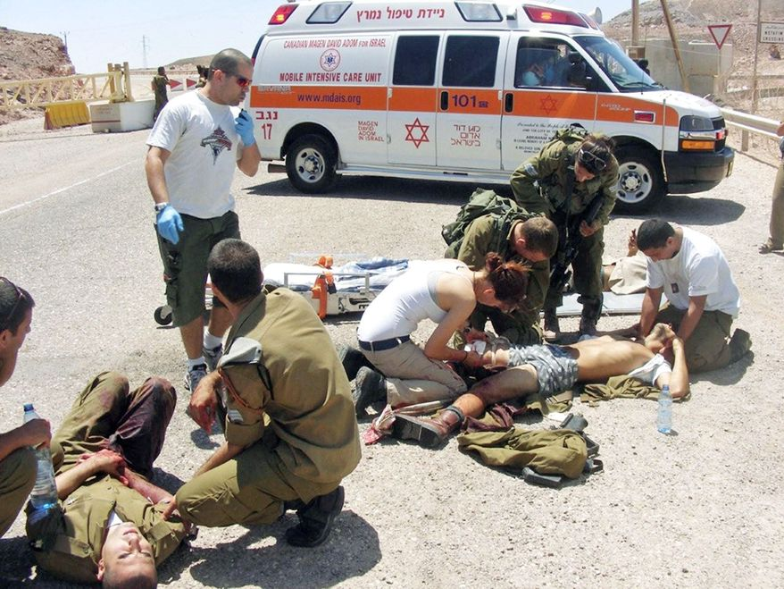 AFTERMATH: Israeli soldiers are treated Thursday after a shooting attack along the border between Israel and Egypt. Assailants armed with heavy weapons and explosives crossed into southern Israel from the Sinai Peninsula, killing eight Israelis and wounding at least a dozen in Eilat. (Associated Press)