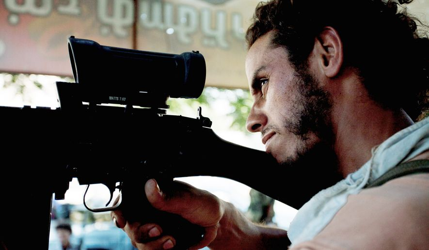 A Libyan rebel sniper peers through his scope in Sabratha, 50 miles west of Tripoli, on Wednesday. Regime snipers positioned in tall buildings, including a bank and a hotel, take aim at anyone who moves. Rebel fighters, who control the west and south of Zawiyah, say they are confident that they will soon drive out Col. Gadhafi's soldiers entrenched in the east of the city. (Associated Press)