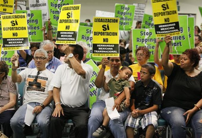 **FILE** Immigrant rights groups and community members call in Los Angeles on Aug. 15, 2011, for an end to the Department of Homeland Security's (DHS) Secure Communities program, which was created in 2008 and calls for police to submit suspects' fingerprints to DHS so they can be cross-checked with federal deportation orders. (Associated Press)