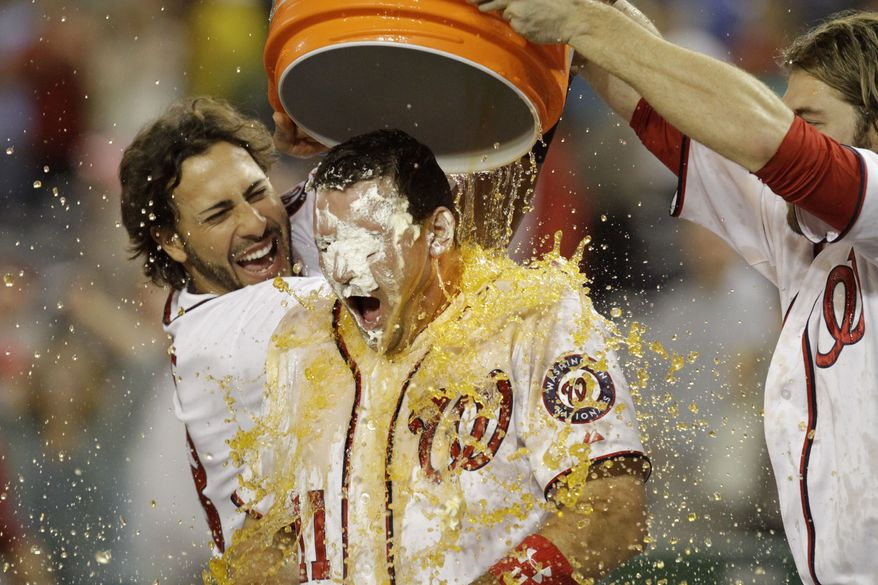 Washington Nationals Michael Morse and Jayson Werth pour Gatorade over Nationals Ryan Zimmerman after Zimmerman hit a walk off grand slam against the Philadelphia Phillies on Friday night. The Nationals won 8-4. (AP Photo/Jacquelyn Martin)