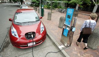 ** FILE ** A Nissan Leaf charges at a station in Portland, Ore. (Associated Press)