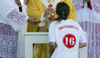 Associated Press Pope Benedict XVI serves Communion to a girl wearing a T-shirt bearing his name while celebrating Mass at Cuatro Vientos airfield outside Madrid on Sunday. The pope was in Madrid for the four-day World Youth Day event that drew 1.5 million.