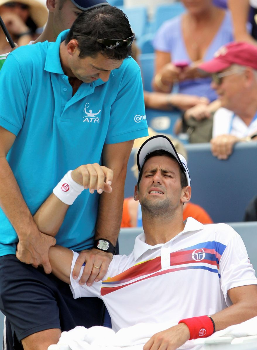 ASSOCIATED PRESS Novak Djokovic, the top-ranked player in the world, has his shoulder worked on before retiring in the Western & Southern Open.