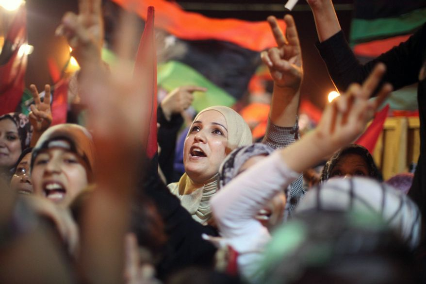 People celebrate in Benghazi.  Libyan rebels raced into Tripoli in a lightning advance Sunday that met little resistance as Moammar Gadhafi's defenders melted away and his 40-year rule appeared to rapidly crumble.  (AP Photo/Alexandre Meneghini)