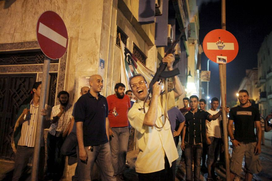 A man shoots to the sky as he celebrates the capture in Tripoli of Moammar Gadhafi's son and one-time heir apparent, Seif al-Islam, at the rebel-held town of Benghazi, Libya, early Monday, Aug. 22, 2011.  (AP Photo/Alexandre Meneghini)