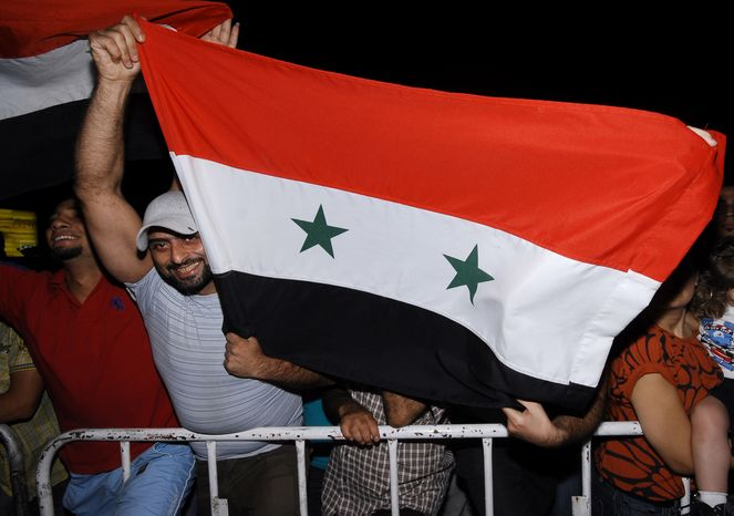 A supporter of Syrian President Bashar Assad waves the Syrian flag as he demonstrates his solidarity with the leader in Damascus, Syria, on Friday, Aug. 19, 2011. (AP Photo/Muzaffar Salman)