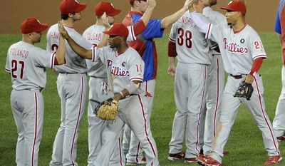 Philadelphia Phillies' Placido Polanco,  Jimmy Rollins, Wilson Valdez and teammates celebrate their 5-0 win over the Washington Nationals on Saturday in Washington. (AP Photo/Nick Wass)