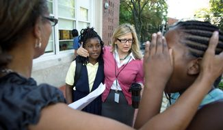 Principal Jennifer Frentress welcomes Monica Jackson, 10, and other students on the first day of the school year at John Tyler Elementary in Southeast. (Rod Lamkey Jr./The Washington Times)