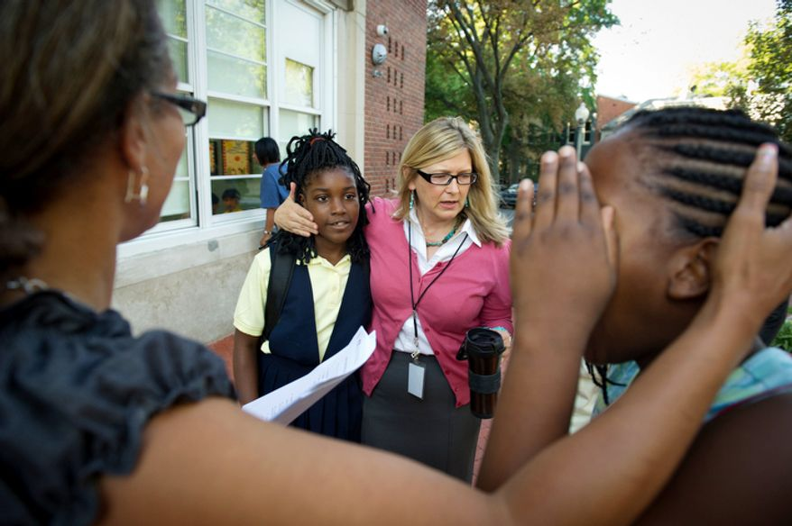 John Tyler Elementary School Principal Jennifer Frentress (right) puts her arm around student Monica Jackson, 10, (left) as students and their parents arrive for the first day of school. (Rod Lamkey Jr./The Washington Times)