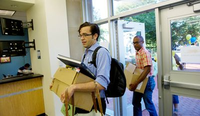 Third grade Spanish teacher Andres Harris (left) gets help carrying school supplies to his classroom from friend Jeremi Jones on the first day of school at John Tyler Elementary School. (Rod Lamkey Jr./The Washington Times)