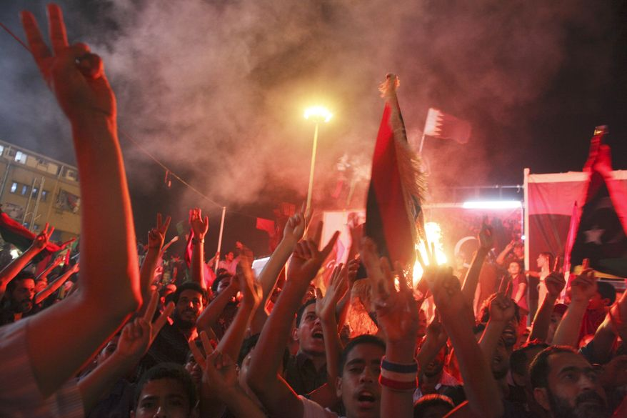 Libyans in the rebel-held town of Benghazi, Libya, celebrate the capture in Tripoli of Col. Moammar Gadhafi's son and one-time heir apparent, Seif al-Islam, early on Monday, Aug. 22, 2011. (AP Photo/Alexandre Meneghini)