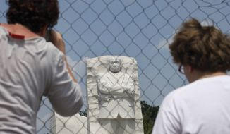 Visitors to the Rev. Martin Luther King Jr. Memorial take pictures behind security fencing on the National Mall in Washington on Aug., 21, 2011. (Associated Press)
