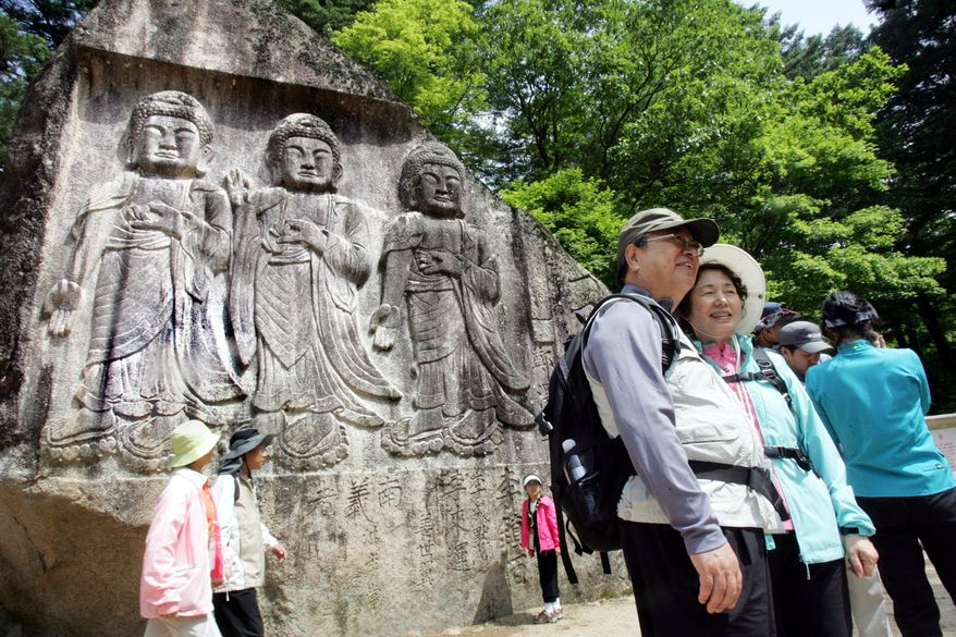 ** FILE ** South Korean tourists pose in front of the Sambulam, the three Buddha sculpture, on Diamond Mountain in June 2007. (AP Photo/Ahn Young-joon, File)
