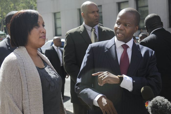Nafissatou Diallo, the hotel housekeeper who accused Dominique Strauss-Kahn of sexually assaulting her, listens as her lawyer Kenneth Thompson speaks to the media following a meeting at the Manhattan prosecutor's office on Aug. 22, 2011. (Associated Press)