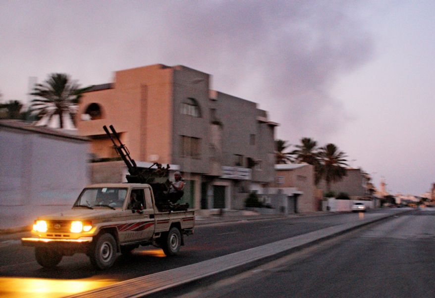 An armured vehicle speeds on the outskirts of Tripoli, as huge smoke rises over the downtown, late Monday, Aug. 22, 2011. Moammar Gadhafi's whereabouts remained unknown.  (AP Photo/Sergey Ponomarev)