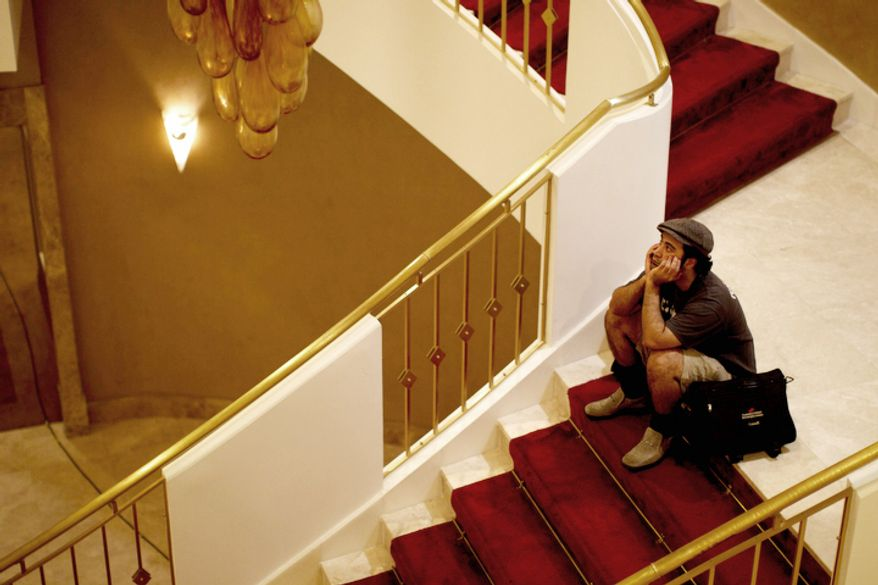 A journalist sits on the stairs of the Rixos hotel in Tripoli, Libya. The  hotel housed top government officials, foreign journalists and state television facilities but the hotel is is still in control of forces loyal to Libya's Moammar Gadhafi and only dozens of journalist remain trapped, unable to leave. (AP Photo/Dario Lopez-Mills)