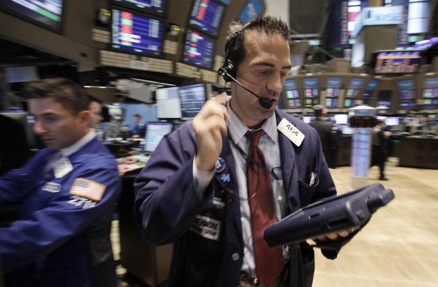 Trader Gregory Rowe (right) works on the floor of the New York Stock Exchange on Aug. 22, 2011. (Associated Press)