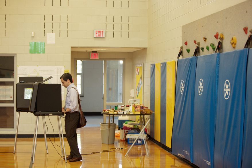 Tyler Rosen casts his primary ballot Tuesday at Arlington Traditional School in the Ballston neighborhood. Voter turnout for Virginia's primary elections was light. (Andrew Harnik/The Washington Times)