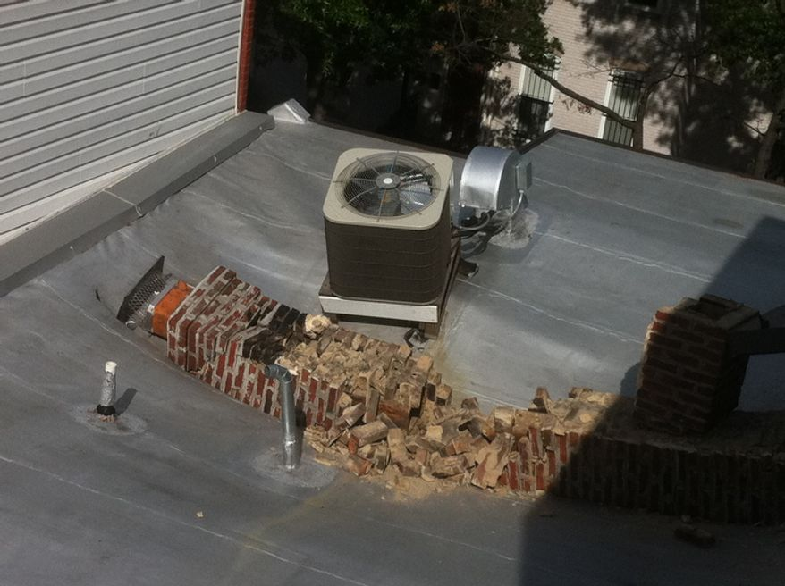 A rowhouse at 5th Street and Florida Ave., NW has roof damage after its chimney collapses as a result of a 5.8 earthquake in Virginia has been felt in Washington, D.C., Tuesday, August 23, 2011. (Andrew Harnik / The Washington Times)