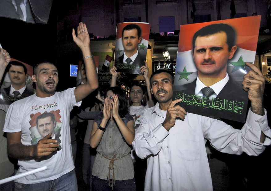 """Supporters of Syrian President Bashar Assad carry his picture as they shout pro-regime slogans during a demonstration in Damascus, Syria, on Monday, Aug. 22, 2011. The Arabic on picture reads, """"You protect our home; peace be upon you."""" (AP Photo/Muzaffar Salman)"""