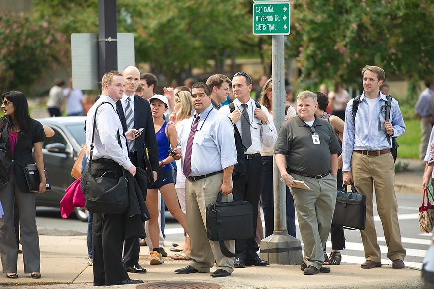 People react and make their way from Arlington Gateway Park in Rosslyn, Va, Tuesday, August 23, 2011, after a 5.9 earthquake which struck at around 2pm EST, with an epicenter outside of Richmond, Va. (Rod Lamkey Jr./The Washington Times)