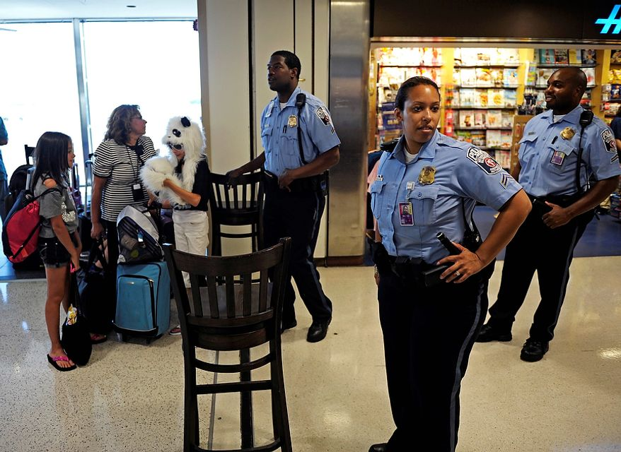 Ronald Reagan National Airport Police stop travelers from entering Terminal A, Tuesday, Aug. 23, 2011, as authorities checked for damage after an earthquake in the Washington area. A 5.9 magnitude earthquake centered in Virginia forced evacuations of all the monuments on the National Mall in Washington and rattled nerves from Georgia to Martha's Vineyard, the Massachusetts island where President Barack Obama is vacationing. No injuries were immediately reported.  (AP Photo/Cliff Owen)