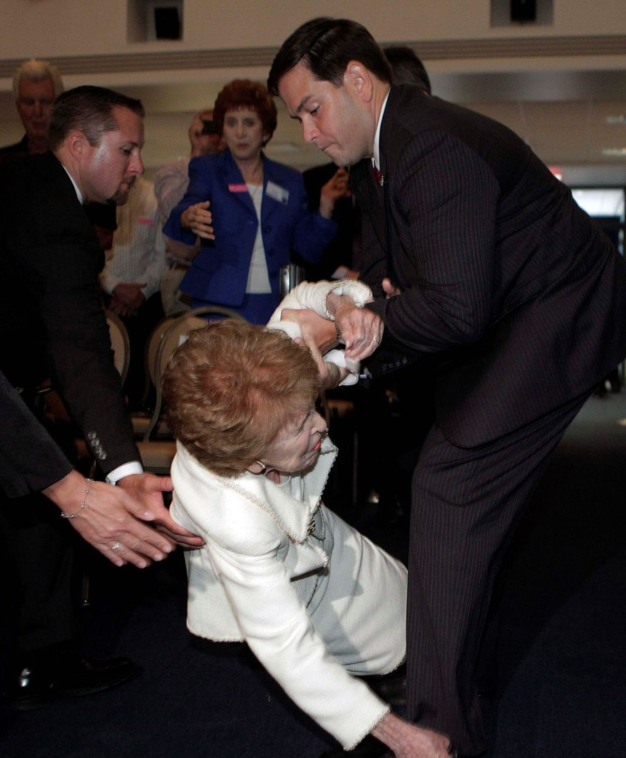 ASSOCIATED PRESS Former first lady Nancy Reagan is helped by Sen. Marco Rubio, Florida Republican, as she falls at the Ronald Reagan Presidential Library in Simi Valley, Calif. Mrs. Reagan, 90, had invited Mr. Rubio to speak at a forum in the library there. Several people rushed to help her as she stumbled. A spokeswoman for the former first lady said she wasn't hurt after tripping over a crowd-control post.
