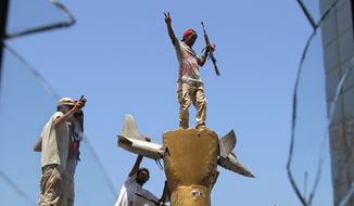 Rebel fighters celebrate as they stand on top of the monument inside the main Moammar Gadhafi compound in Bab Al-Aziziya in Tripoli, Libya, on Aug. 24, 2011. (Associated Press)
