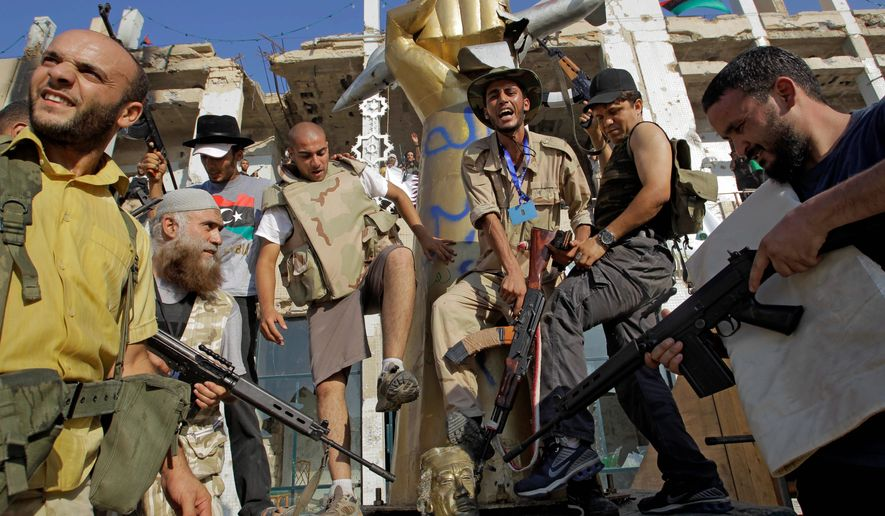 Rebel fighters stomp on a part of a statue of Col. Moammar Gadhafi after overtaking the Libyan leader's Bab al-Aziziya compound in Tripoli on Tuesday. The rebels stormed the military compound after fierce fighting with forces loyal to the regime. Col. Gadhafi was not found inside the walls. His whereabouts were not immediately known. (Associated Press)