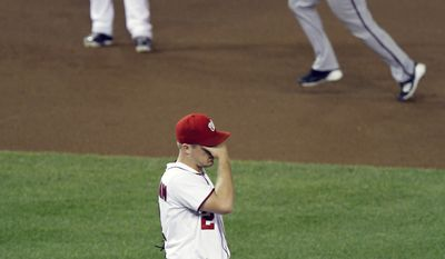 Washington Nationals pitcher Jordan Zimmermann wipes his head after Arizona Diamondbacks' Sean Burroughs hit a two-run home run in the seventh inning. The Nats lost 2-0. (AP Photo/Luis M. Alvarez)