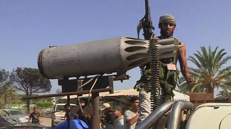 In this image made from television, rebel fighter stands on the back of a truck with an rocket launcher in Moammar Gadhafi's Bab al-Aziziya