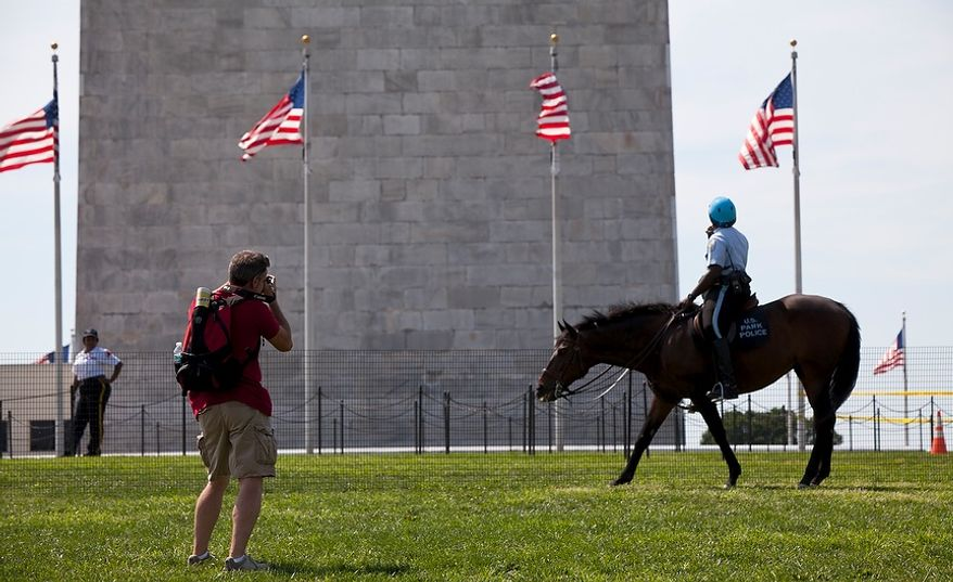 Dave Southward of Hamilton, Ontario, takes photos of the Washington Monument in D.C., behind a temporary barrier set up by the U.S. Park Police on Aug. 24, 2011. The monument will be closed for an indefinite period of time while the National Park Service inspects it for damage resulting from the 5.8-magnitude earthquake that hit the East Coast on Aug 23, 2011. (Pratik Shah/The Washington Times)