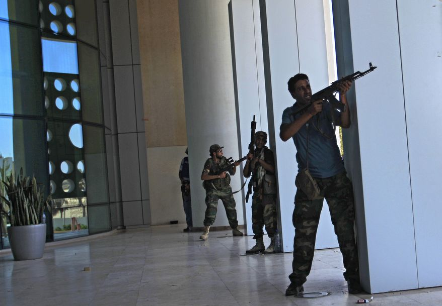 """Rebel fighters take cover as a gunbattle erupts Thursday outside the Corinthia Hotel in Tripoli, LIbya. Rebel leadership has offered a $1.7 million bounty for fugitive dictator Moammar Gadhafi. Speaking to a local television channel Wednesday, apparently by phone, Col. Gadhafi vowed from hiding to fight on """"until victory or martyrdom."""" (Associated Press)"""