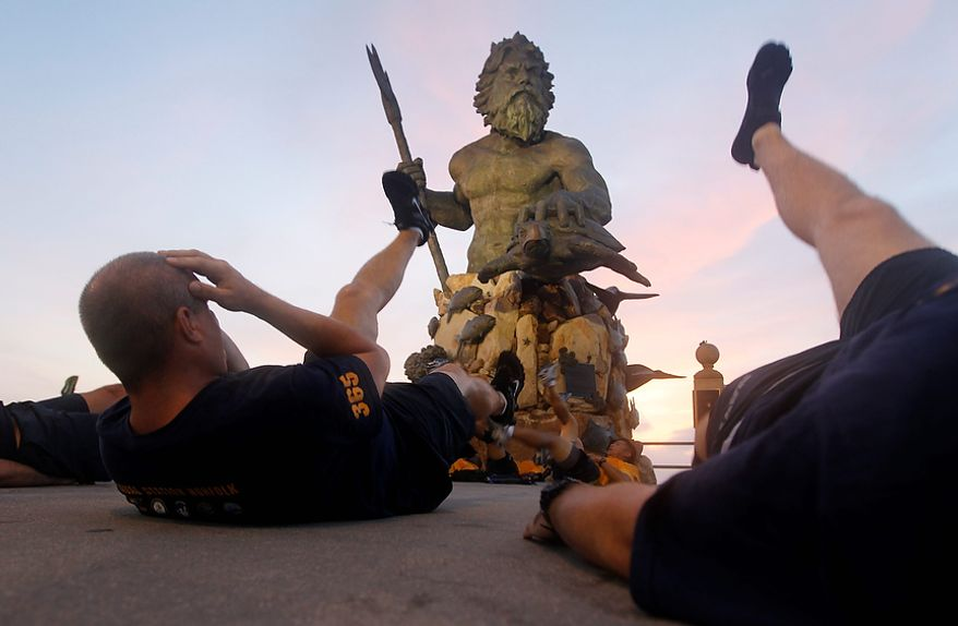 US Navy Chief Petty Officers conduct physical training in front of a statue of Neptune on the oceanfront of Virginia Beach, Va., Friday, Aug. 26, 2011.  Hurricane Irene is expected to hit the area Saturday.  (AP Photo/Steve Helber)
