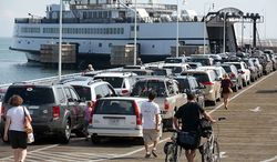 ** FILE ** Passengers with cars and bicycles prepare to board a ferry departing the island of Martha's Vineyard, in Oak Bluffs, Mass., Friday, Aug. 26, 2011. (AP Photo/Steven Senne)