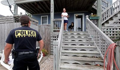 Nags Head police officer Edward Mann speaks with resident Debbie Hickey about Hurricane Irene as it approaches the Outer Banks in Nags Head, N.C., Friday, Aug. 26, 2011. Mann was warning residents who have not evacuated that assistance will be limited after the storm winds reach 60 miles per hour. (AP Photo/Gerry Broome)