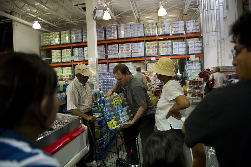 Joey Yalowitz (center) of Huntsville, Ala., helps a man with a case of bottled water at discount warehouse club Costco in Arlington, Va., on Aug. 26, 2011, a day before Hurricane Irene was expected to hit the D.C. region. (Rod Lamkey Jr./The Washington Times)