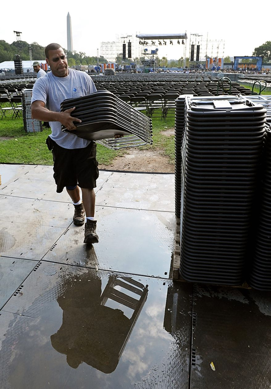 A worker packs-up a portion of the 30,000 chairs at the Martin Luther King, Jr. Memorial in Washington, Friday, Aug. 26, 2011. The memorial's dedication ceremony has been postponed due to the impending arrival of Hurrican Irene.  (AP Photo/Cliff Owen)