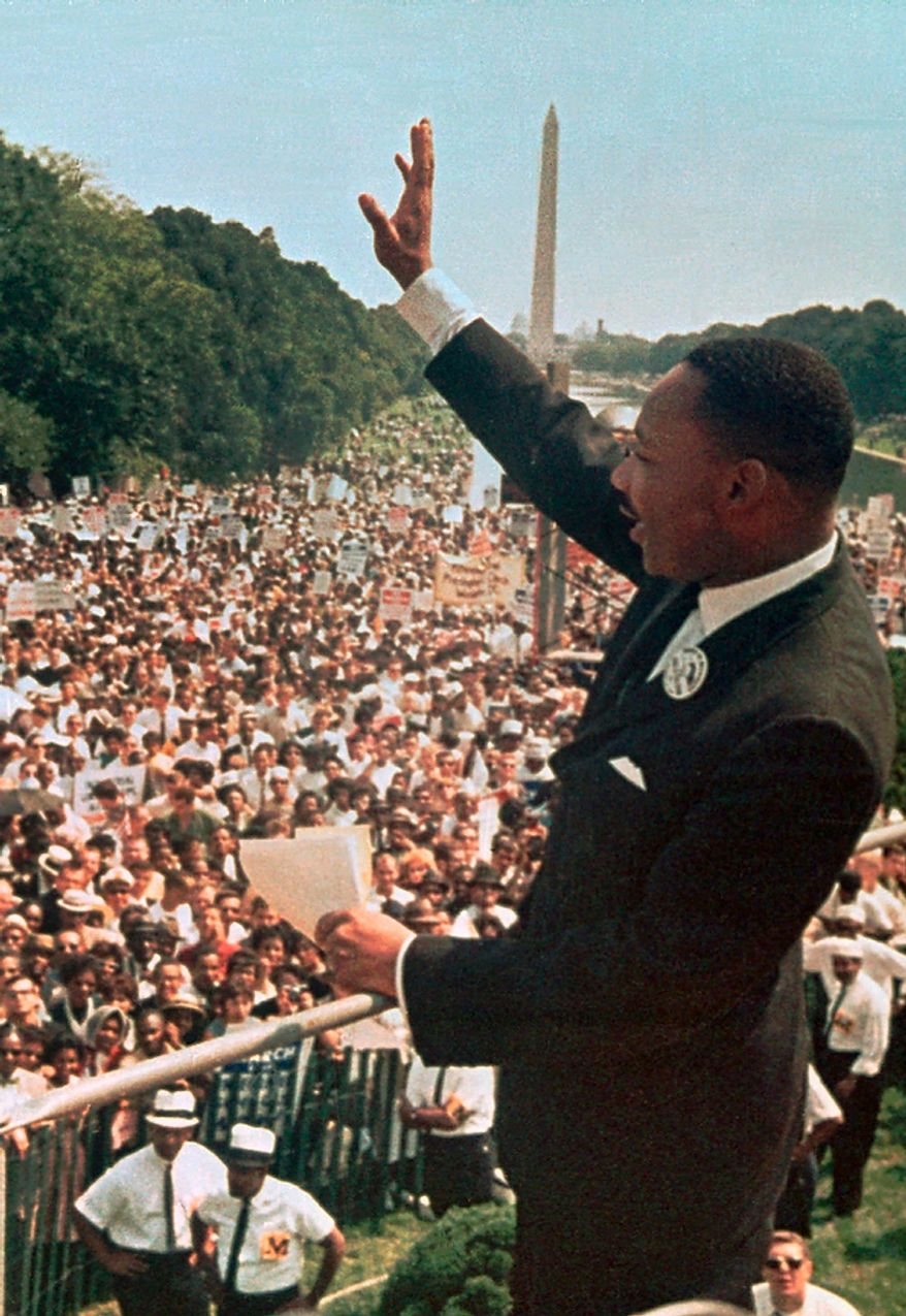 """This Aug. 28, 1963, file photo shows Dr. Martin Luther King Jr. acknowledging the crowd at the Lincoln Memorial for his """"I Have a Dream"""" speech during the March on Washington. Monday, Jan. 17, 2011, marks the 25th federal observance of the birth of King, one of America's most celebrated citizens, and the only non-U.S. president to be honored with a national holiday.  (AP Photo/File)"""