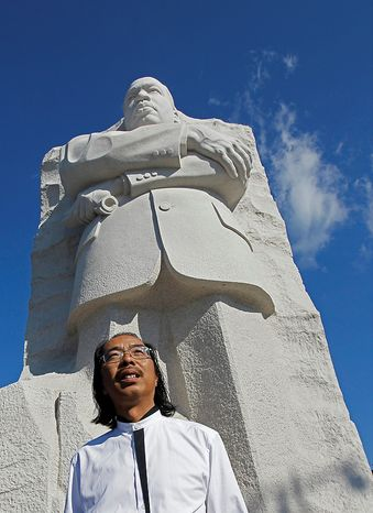 Sculptor Lei Yixin, from China, poses in front of the Martin Luther King, Jr. Memorial ahead of its dedication this weekend in Washington, Monday, Aug. 22, 2011. (AP Photo/Charles Dharapak)