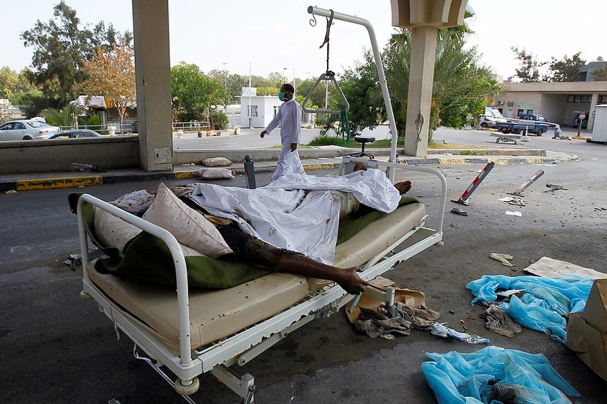 Libyan dead bodies lay in the hospital of Abu Salim district, in Tripoli, Libya, Friday, Aug. 26, 2011. The four-story hospital was completely empty with shattered glass over the floors, dark with dried blood stains and with medical equipment strewn about.  In the hospital yard next to the parking lot is a pile of 20 decomposing bodies, all of them darker skinned than most Libyans, covered with blankets. Gadhafi had recruited fighters from sub-Saharan Africa.(AP Photo/Francois Mori)