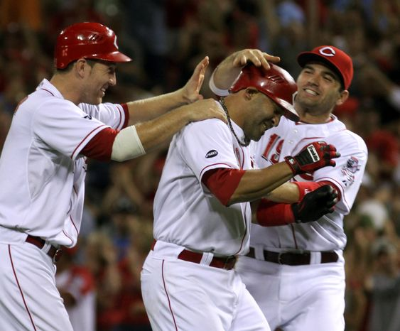 Cincinnati Reds Miguel Cairo, center, gets congratulated by teammates Todd Frazier, left, and Joey Votto after hitting a single in the bottom of the ninth inning against the Washington Nationals to score Drew Stubbs to win the game 4-3 in Cincinnati on Friday, Aug. 26, 2011. (AP Photo/Tom Uhlman)