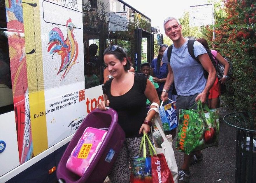 "Marco and Marta Bonifazi of Geneva return to the bus that will take them back home to Geneva after their first shopping trip at the Carrefour supermarket across the border in Ferney-Voltaire, France. ""It's just great to save money,"" Mr. Bonifazi, showing off his receipt, said of the Swiss franc that buys a lot more in countries that use the euro. (Associated Press)"