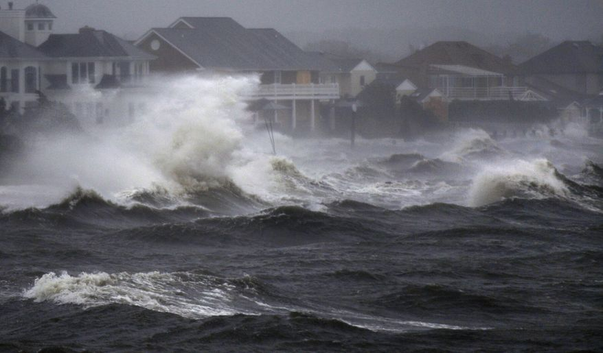 Waves from a storm surge from Hurricane Irene crash over the shore during high tide in Bayshore, N.Y., on Long Island on Sunday, Aug. 28, 2011. (AP Photo/Charles Krupa)